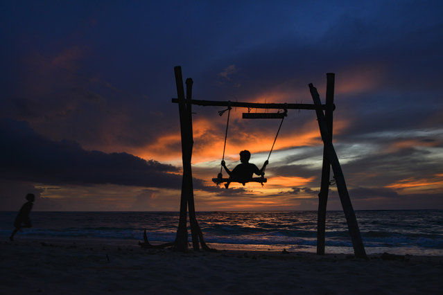 A child plays in a swing as the sun sets at Lhoknga beach in Aceh province, Indonesia on December 9, 2019. (Photo by Chaideer Mahyuddin/AFP Photo)