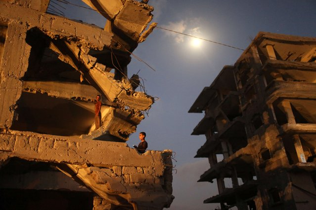 Palestinian boys stand inside their damaged home in al-Tufah, in the east of Gaza City on July 27, 2015, during a power outage. Residents of Gaza, home to 1.8 million people, have been experiencing up to 15 hours of electricity outage a day for the past two weeks due to fuel and power shortages. (Photo by Mahmud Hams/AFP Photo)