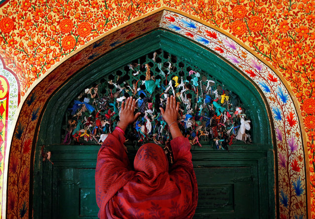 A woman prays at the shrine of Sufi Saint Khawaja Naqshband during the holy fasting month of Ramadan in Srinagar, June 20, 2017. (Photo by Danish Ismail/Reuters)