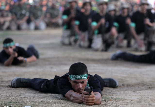 Young Palestinians hold pistols to display their military skills during a graduation ceremony of the Hamas, Liberation Youth, military summer camp, in Gaza City, Wednesday, August 5, 2015. (Photo by Khalil HamraAP Photo)