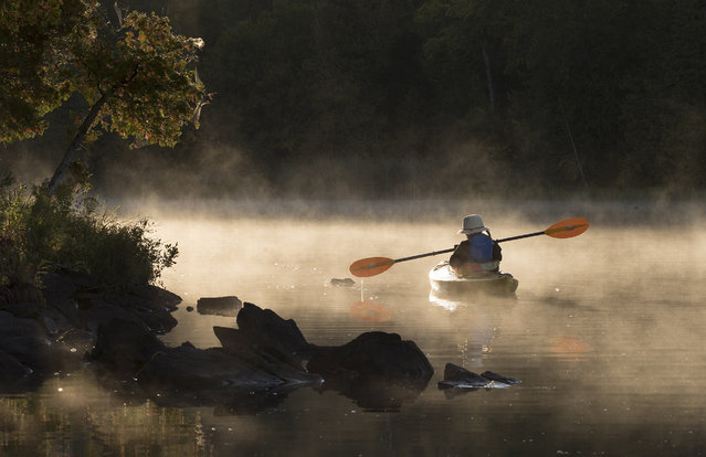 A kayaker paddles through morning mist on Pigeon Lake in Kawartha Lakes in central Ontario on Tuesday September 17, 2019. (Photo by Fred Thornhill/The Canadian Press via AP Photo)