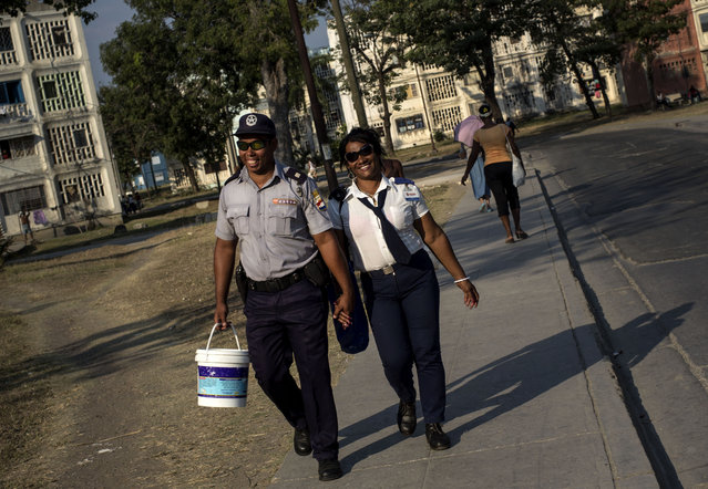 In this March 20, 2015 photo, a couple walk hand-in-hand after work in Santiago, Cuba. He wears a national police officer uniform and she wears a state security guard uniform. (Photo by Ramon Espinosa/AP Photo)