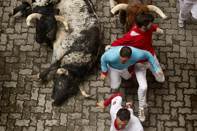"""Revelers run with Torrestrella ranch fighting bulls during the running of the bulls of the San Fermin festival, in Pamplona, Spain, Monday, July 7, 2014. Revelers from around the world arrive in Pamplona every year to take part on some of the eight days of the running of the bulls glorified by Ernest Hemingway's 1926 novel """"The Sun Also Rises"""". (Photo by Daniel Ochoa de Olza/AP Photo)"""
