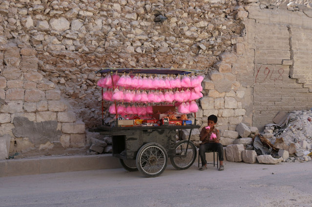 A Syrian child eats candy floss while selling it on a street cart in the Syrian city of al- Bab in the northern Aleppo province on May 15, 2017. (Photo by Zein Al Rifai/AFP Photo)