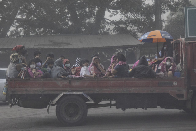 Residents fleeing Taal Volcano's eruption ride a flatbed truck on January 13, 2020 in Lemery, Batangas province, Philippines. The Philippine Institute of of Volcanology and Seismology raised the alert level to four out of five, warning that a hazardous eruption could take place anytime, as Manila's international airport suspended flights and authorities began evacuating tens of thousands of people from the area. (Photo by Ezra Acayan/Getty Images)