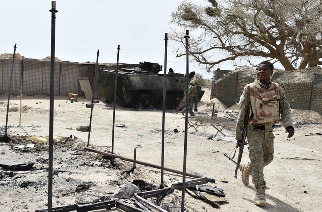 A soldier walks past a damaged army personnel carrier, June 17, 2016, in the military camp in Bosso. Boko Haram on June 9 attacked a military post in Bosso in Niger's Diffa region, killing 26 soldiers. (Photo by Issouf Sangoissouf Sanogo/AFP Photo)