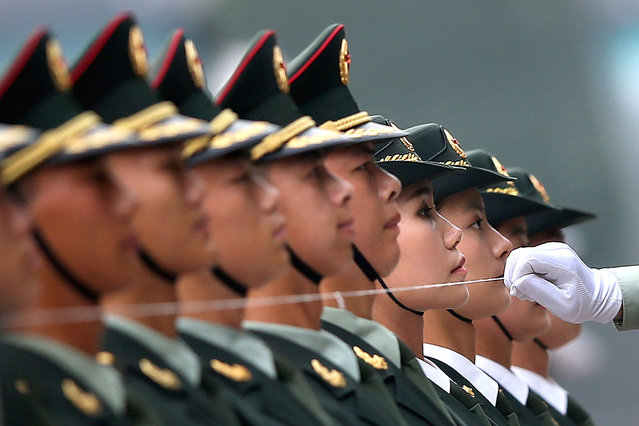 An officer of a Chinese People's Liberation Army (PLA) honour guard uses a string to ensure members of the honour guard are standing in a straight line, before a welcoming ceremony for Germany's Chancellor Angela Merkel outside the Great Hall of the People in Beijing July 7, 2014. (Photo by Feng Li/Getty Images)