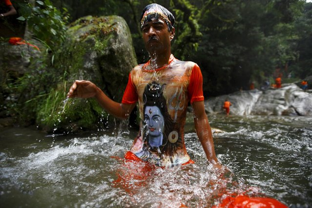 "A Hindu devotee wearing a t-shirt printed with a portrait of Lord Shiva takes a holy dip while participating in the ""Bol Bom"" pilgrimage in Kathmandu August 10, 2015. (Photo by Navesh Chitrakar/Reuters)"
