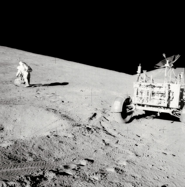 "Astronaut David R. Scott, mission commander, with tongs and gnomon in hand, studies a boulder on the slope of Hadley Delta during the Apollo 15 lunar surface extravehicular activity. The Lunar Roving Vehicle (LRV) or Rover is in right foreground. View is looking slightly south of west. ""Bennett Hill"" is at extreme right. Astronaut James B. Irwin, lunar module pilot, took this photograph. (Photo by NASA)"