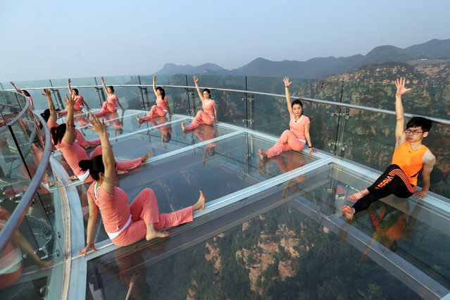People practise yoga at a tourist spot ahead of the International Day of Yoga, on the outskirts of Beijing, China, June 20, 2016. (Photo by Reuters/China Daily)