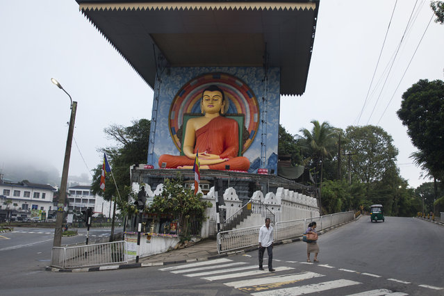 In this November 17, 2019, photo, commuters walk past a statue of Buddha in Kandy, Sri Lanka. In this mountain city that was for centuries home to Sri Lanka's kings and in recent years has been riven by religious violence, Buddhist nationalists are rejoicing the election of the country's newest leader. They hope he ushers in another golden era for the nation's ethnic majority. Buddhist nationalism has been on the rise, and it was thrust to the forefront of Sri Lankan politics after Islamic State-inspired suicide attacks by local militants killed 269 people at churches and hotels on Easter Sunday. (Photo by Dar Yasin/AP Photo)