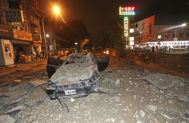 A crushed vehicle sits in rubble on a destroyed street after multiple explosions from an underground gas leak in Kaohsiung, Taiwan, early Friday, August 1, 2014. A massive gas leakage early Friday caused five explosions that killed several people and injured over 200 in the southern Taiwan port city of Kaohsiung. (Photo by AP Photo)