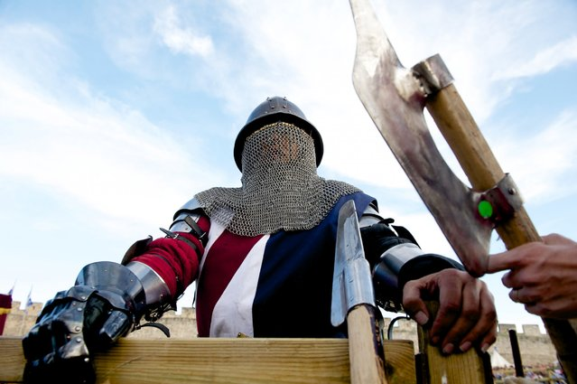 """A member of the American armored combat league team, the USA Knights, chooses a weapon before combat during the International Medieval Combat at the castle of Belmonte, May 1, 2014, in Belmonte, Spain. """"All the edges on weapons have to be 2-millimeter wide"""", said USA Knights team captain Andre Sinou. """"We'll go over the blades... so that there are no sharp edges that could puncture"""". (Photo by Juan Naharro Gimenez/Getty Images)"""