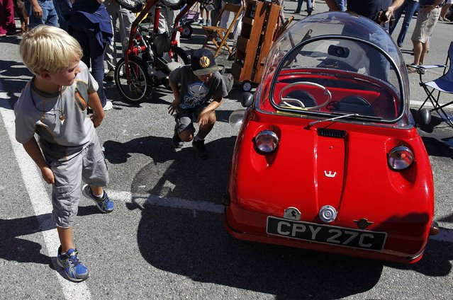 Children look at a 1964 Peel Trident during the Little Car Show in Pacific Grove, California, August 13, 2014. The event, which showcases small cars with up to 1,601cc engines as well as electric cars, is held during the Pebble Beach Automotive Week which culminates with the Concours d'Elegance. (Photo by Michael Fiala/Reuters)