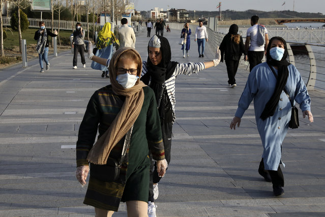 People wearing face masks exercise on the shore of an artificial lake, in Western Tehran, Iran, Sunday, March 15, 2020. Many people in Tehran shrugged off warnings over the new coronavirus as authorities complained that most people in the capital are not treating the crisis seriously enough. For most people, the new coronavirus causes only mild or moderate symptoms. For some it can cause more severe illness. (Photo by Vahid Salemi/AP Photo)