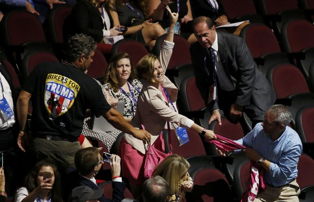 Alli McCracken of the activist group Code Pink wrestles with convention attendees as she shouts during the evening session at the Republican National Convention in Cleveland, Ohio, U.S. July 18, 2016. (Photo by Carlo Allegri/Reuters)