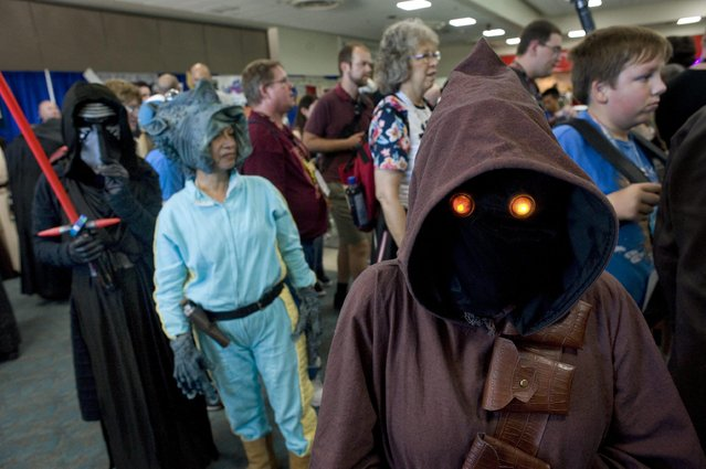 A cosplayer (R) dressed as a Jawa, a fictional species from the Star Wars universe, poses for a photo during Comic Con 2016 in San Diego, California, USA, 22 July 2016. (Photo by David Maung/EPA)