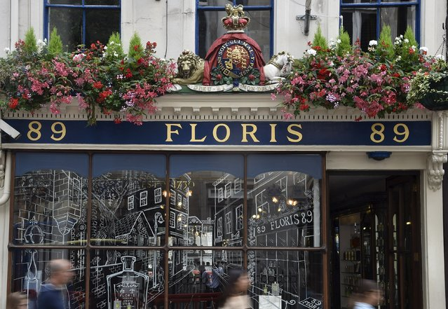 Shoppers walk past the shopfront of Floris with a royal warrant design above it in central London, Britain, August 19, 2015. Floris, established in 1730, holds a warrant as perfumer to Queen Elizabeth. (Photo by Toby Melville/Reuters)