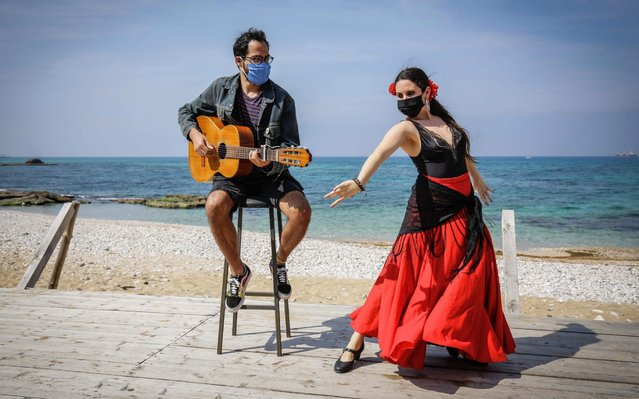 Argentinian dancer Maria Belen Ciaschi, stranded in Lebanon due to COVID-19 coronavirus pandemic, dances flamenco to the music played by Uruguayan singer Walter Javier Maulelo while both wearing a mask on a seafront boardwalk in the northern coastal city of Batroun, on April 15, 2020. (Photo by Ibrahim Chalhoub/AFP Photo)