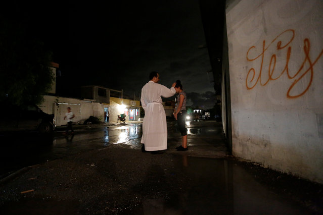Catholic priest Jose Luis Fernandez, a member of Raza Nueva in Christ, a project of the archdiocese of Monterrey, blesses a young woman during a visit to a neighbourhood in the municipality of Garcia, on the outskirts of Monterrey, Mexico, June 1, 2016. (Photo by Daniel Becerril/Reuters)