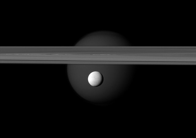 A brightly reflective Enceladus appears before the rings of Saturn, while the planet's larger moon Titan looms in the distance. Enceladus (313 miles, or 504 kilometers across) is in the center of the image. Titan (3,200 miles, or 5,150 kilometers across) glows faintly in the background beyond the rings, in this image acquired by NASA's Cassini spacecraft on March 12, 2012. (Photo by NASA/JPL-Caltech/Space Science Institute)