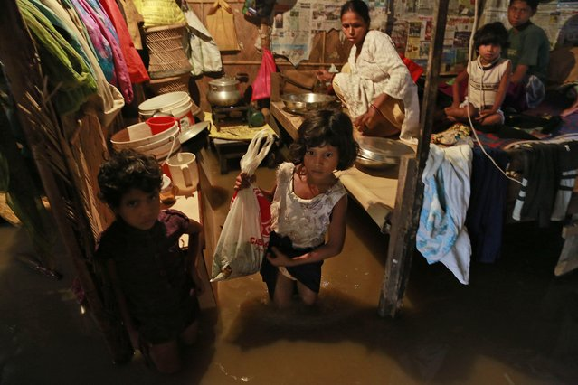 An Indian girl walks with a plastic bag inside a flooded house in Gauhati, India, Friday September 5 2014. Heavy monsoon showers flooded some areas in the city on Friday. (Photo by Anupam Nath/AP Photo)