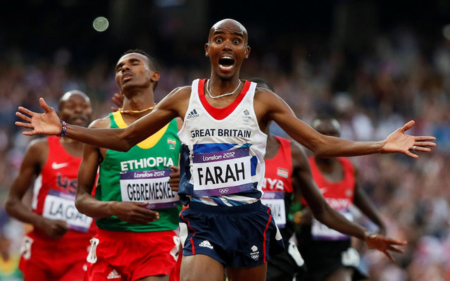 "Britain's Mo Farah reacts as he wins the men's 5000m final at the London 2012 Olympic Games at the Olympic Stadium in Britain August 11, 2012. Lucy Nicholson: ""When Mo Farah was rounding the final corner for the 5000m the huge stadium was electric, everybody was on their feet and he knew he was going to win as he came into that final stretch. All the photographers were excited because we knew he was going to react in a very dramatic way so it was a lovely sequence of photos as he crossed the finish line – he put his hands over his head, he wrapped himself in the British flag, it was a very long celebration sequence, which is all you can really wish for as a photographer"". (Photo by Lucy Nicholson/Reuters)"