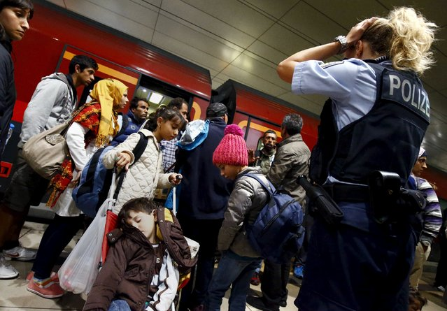 A German border police woman reacts after dozens of migrants unexpectedly disembarked a train that departed from Budapest's Keleti station at the railway station of the airport in Frankfurt, Germany, early morning September 6, 2015. Austria and Germany threw open their borders to thousands of exhausted migrants on Saturday, bussed to the Hungarian border by a right-wing government that had tried to stop them but was overwhelmed by the sheer numbers reaching Europe's frontiers. (Photo by Kai Pfaffenbach/Reuters)
