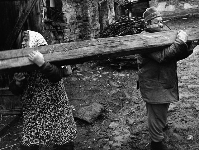 "A love story with two log choppers. ""In 1993, I was working on a project about life in the Olomouc region of Czechoslovakia. One day, I came to the village of Dlouhá Loučka-Křivá and went into a courtyard where I saw two old people, a husband and wife, sawing firewood for winter. They were working quietly, concentrating. I watched them fetch a beam from a wrecked barn, but they didn't discuss how they planned to carry it to the saw. The woman faced one way, the man the other. When they realised, the woman eventually turned and followed her husband. The picture I took is the picture of many relationships – when each partner wants something different, but they have to come to an agreement, pull together eventually"". (Photo by Jindrich Streit)"