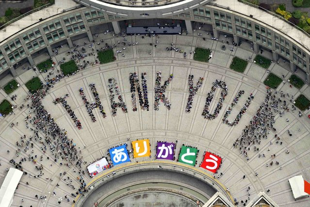 "An aerial view shows people sitting in formation to the words ""thank you"" and displaying signs that collectively read ""Arigato"" (Thank You) during an event celebrating Tokyo being chosen to host the 2020 Olympic Games, at Tokyo Metropolitan Government Building in Tokyo, in this file photo taken by Kyodo September 8, 2013. Tokyo's 2020 Summer Olympics were meant to be different: compact, on budget and on time. (Photo by AFP Photo/Kyodo)"