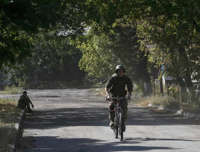 A Ukrainian paratrooper rides on a bicycle near Zhdanivka September 13, 2014. (Photo by Gleb Garanich/Reuters)