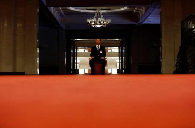 A security officer sits inside the Great Hall of the People during the 19th National Congress of the Communist Party of China in Beijing, China on October 18, 2017. (Photo by Tyrone Siu/Reuters)