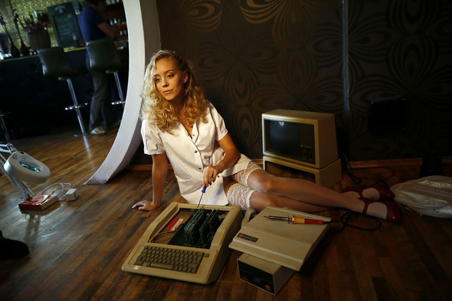 """Model Laura poses with a historic computer during a photo shoot for the """"Nerd Dreams Calendar 2013"""", in Frankfurt September 24, 2012. Harking back to the days of floppy disks, the Nerd Dreams calendar project showcases long-outdated but fondly-remembered computers such as the C64, the Atari ST and Mac SE. The Germany-based team behind this homage to the frontrunners of today's smartphones and tablets PCs are making use of new crowd-funding sites to get financial backing for the project. (Photo by Ralph Orlowski/Reuters)"""