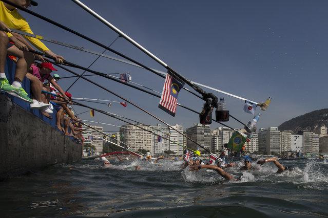 Competitors swim past the feeding station during the women's marathon swimming event at the 2016 Summer Olympics in Copacabana beach, Rio de Janeiro, Brazil, Monday, August 15, 2016. (Photo by Felipe Dana/AP Photo)