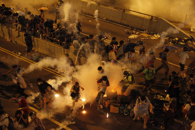Riot police fire teargas to disperse protesters after thousands of demonstrators blocked the main street to the financial Central district outside the government headquarters in Hong Kong September 29, 2014. (Photo by Reuters/Stringer)