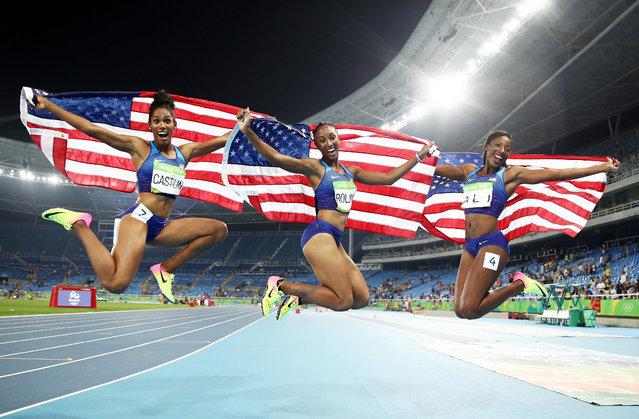 (L-R) Bronze medalist Kristi Castlin, gold medalist Brianna Rollins and silver medalist Nia Ali of the United States celebrate with American flags after the Women's 100m Hurdles Final on Day 12 of the Rio 2016 Olympic Games at the Olympic Stadium on August 17, 2016 in Rio de Janeiro, Brazil. (Photo by Cameron Spencer/Getty Images)