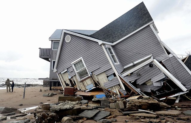 People stand next to a house that collapsed during superstorm Sandy in East Haven, Conn. (Photo by Jessica Hill/Associated Press)
