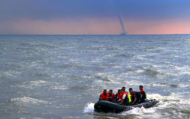 In this US Navy handout photo shows a water spout forming on the horizon, as Bangladeshi Navy divers prepare to board the Military Sealift Command rescue and salvage ship USNS Safeguard (T-ARS 50) on September 27, 2014 for training exercises in the Bay of Bengal. The Bangladeshi sailors are working with US Navy divers during Cooperation Afloat Readiness and Training (CARAT) Bangladesh 2014. (Photo by MC1Tim Miller/AFP Photo/US Navy)