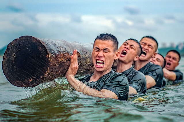 Armed police officers and soldiers carry out the training of pushing logs in the sea. Qinzhou, Guangxi, China, June 16, 2020. (Photo by Costfoto/Barcroft Media via Getty Images)
