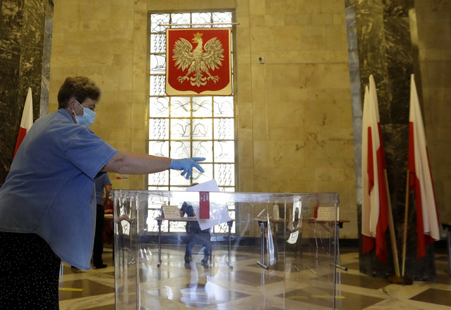 A resident, wearing face mask and protective gloves, casts a vote during presidential election in Warsaw, Poland, Sunday, June 28, 2020. The election will test the popularity of incumbent President Andrzej Duda who is seeking a second term and of the conservative ruling party that backs him. (Photo by Petr David Josek/AP Photo)