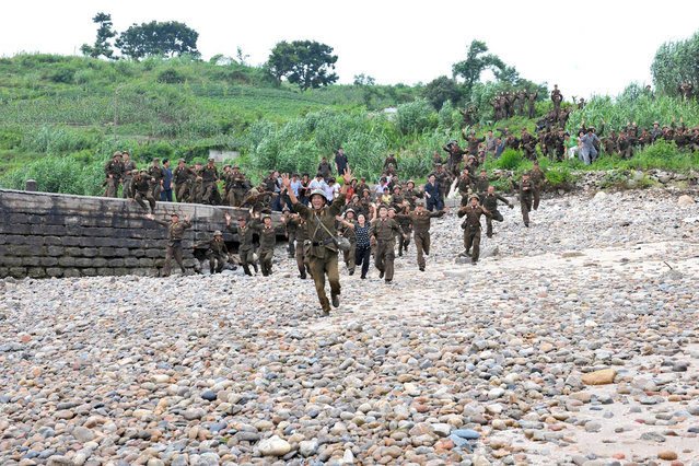 North Korean soldiers and residents run to greet North Korean leader Kim Jong-Un (not pictured) as he arrives to visit a military unit on an island southwest of Pyongyang, August 19, 2012. (Photo by Reuters/KCNA)