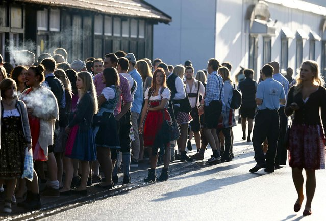 Visitors, most of them in traditional Bavarian dresses, stand in a queue ahead of the opening of the 182nd Oktoberfest in Munich, Germany, September 19, 2015. (Photo by Michael Dalder/Reuters)