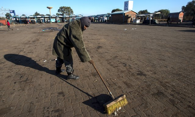 A worker sweeps the floor at a taxi rank in Katlehong, South Africa, Monday, June 22, 2020, as taxi drivers affiliated to the SA National Taxi Council (Santaco) protested against what it believes to be insufficient government relief offered to the industry. South Africa's largest city, Johannesburg, has been hit by a strike by mini-bus taxis, preventing many thousands of people from getting to work on Monday, as the country reopens its economy even as cases of COVID-19 are increasing. (Photo by Themba Hadebe/AP Photo)