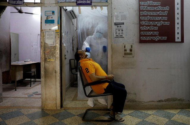 A health worker in personal protective equipment (PPE) collects a sample using a swab from a person at a local health centre to conduct tests for the coronavirus disease (COVID-19), amid the spread of the disease, in New Delhi, India on June 27, 2020. (Photo by Adnan Abidi/Reuters)