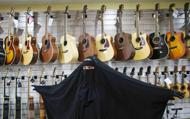 Gisele Marie, a Muslim woman and professional heavy metal musician, gestures in front of a wall of guitars, at a shop selling musical instruments in Sao Paulo August 13, 2015. (Photo by Nacho Doce/Reuters)