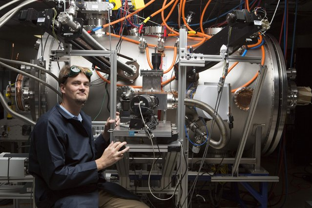 Tom McGuire stands next to the compact fusion reactor experiment inside his lab at the Skunk Works in Palmdale, California, as pictured in this undated handout photo provided by Lockheed Martin. Lockheed Martin Corp said October 15, 2014, that it had made a technological breakthrough in developing a power source based on nuclear fusion, and the first reactors, small enough to fit on the back of a truck, could be ready for use in a decade. (Photo by Reuters/Lockheed Martin)