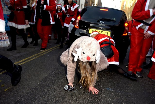 This Rudolph seems like she's had a bit too much, and has fallen over during Santacon day in London, UK, on December 9, 2017. Thousands of drunken people descend on London's Trafalgar square for the annual Santacon event. Participants dress up as Santa Claus before going around the pubs and bars of central London. (Photo by Flynet Pictures)