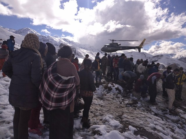 People gather near a helicopter belonging to Nepal Army used to rescue avalanche victims at Thorang-La in Annapurna Region in this October 15, 2014 handout photo provided by Nepal Army. At least 12 people, including eight foreign hikers and a group of yak herders, were killed in Nepal by unseasonal blizzards and avalanches triggered by the tail of cyclone Hudhud, officials said on Wednesday. (Photo by Reuters/Nepalese Army)
