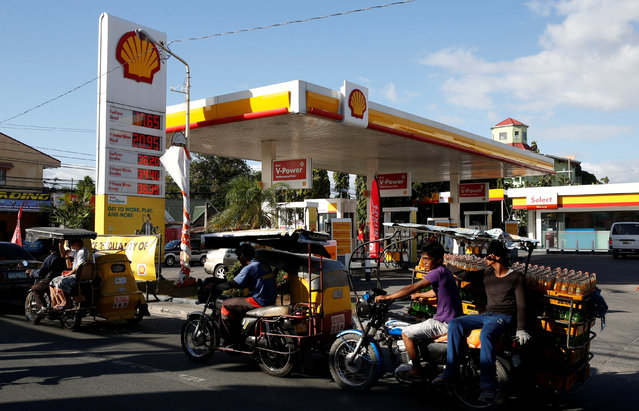 Residents transport commuters and soda bottles on tricycles past a Shell petrol station in Las Pinas, Metro Manila, January 26, 2016. (Photo by Erik De Castro/Reuters)
