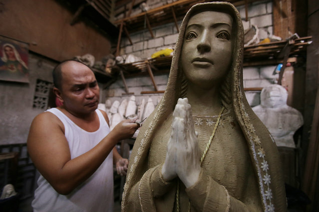 Filipino sculptor Frederic Caedo shapes pottery clay to make an image of the Virgin Mary at his workshop in suburban Quezon city, north of Manila, Philippines on Tuesday, September 29, 2015. Religious images are popular in the Philippines, Asia's largest Roman Catholic nation. (Photo by Aaron Favila/AP Photo)